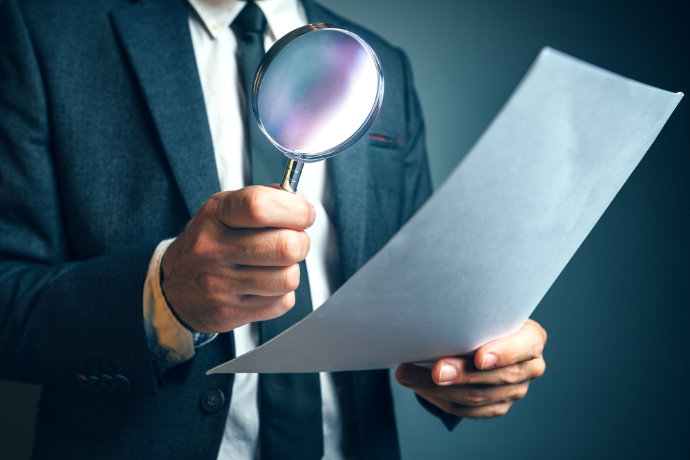 businessman paper magnifying glass